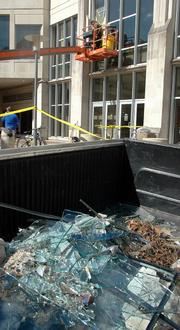 Kansas University Facility Operations personnel work to replace the windows at Budig Hall/Hoch Auditoria. The shards of many windows shattered during Sunday's storm were piled in the back of a truck Tuesday.