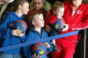 From left, Riley Brown, 11, his cousin Ben Brown, 5, and Ben's brother, Matthew, 2, all from Overland Park, hope to nab player autographs Wednesday as they wait for the Kansas Jayhawks to board a bus at Allen Fieldhouse. The Kansas University team was headed for Auburn Hills, Mich., for Friday's first-round NCAA Tournament game against Bradley University. The boys were with their nanny, Holly White.