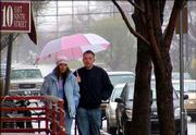 Pedestrians huddle together under an umbrella as they walk downtown.