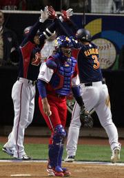 Japan's Toshiaki Imae, left, congratulates Nobuhiko Matsunaka, right, as Cuba's Ariel Pestano walks away after Matsunaka scored on a sacrifice fly in the sixth inning. Japan won the World Baseball Classic championship game, 10-6, Monday in San Diego.