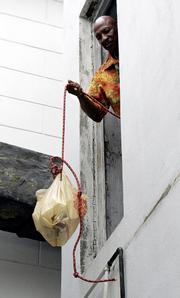 John Powell uses a rope to raise a bag of food into the rectory of St. Augustine Church in New Orleans. The New Orleans Archdiocese has closed the parish but will keep the church open, and Powell and others have taken up residence in the rectory in protest.
