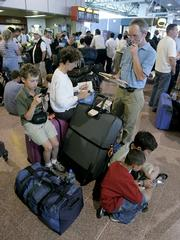 Passengers queue up with their baggage at Heathrow Airport in London. An estimated 30 million bags checked in at airports last year failed to arrive on time with their owners, a new report finds.