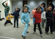 "Center foreground: Marlee Coleman, 5, in blue, and Otulro Hussey, 6, wearing red, take protective stances and yell ""Safe"" during a self-defense, safety and awareness workshop Monday at the Lawrence Public Library. Instruction from the ATA Blackbelt and Leadership Academy came with all three workshops. The academy recently participated in a fundraiser to aid orphans in Mexico and India."