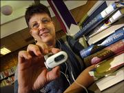 Camille Lechliter, technical services clerk at the Lawrence Public Library displays an MP3 player capable of storing e-audiobooks. On March Ist, the library began to offer downloadable e-audiobooks.