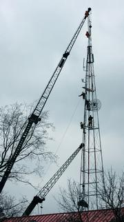 Workers disassemble the radio tower behind Kansas University's Marvin Hall on Tuesday. The 82-year-old tower was damaged in last week's storm.