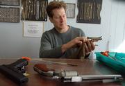 Doug Wahl, owner of Lawrence Pawn and Jewelry, 944 E. 23rd St., cleans a gun at his shop. He says that people who are scared enough to think they need to carry a concealed firearm probably already have one.