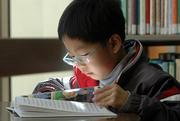 Jeonggyu Kim, 6, Lawrence, looks at a book on Batman at the Lawrence Public Library. A new festival slated for fall 2007 will showcase the benefits of reading.