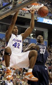 Florida's Al Horford (42) hangs on the rim after dunking against Georgetown's Jeff Green. The Gators beat the Hoyas, 57-53, Friday in Minneapolis.