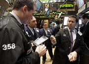 Specialist John Lawlor, right, directs trading in shares of Lucent on the floor of the New York Stock Exchange. Shares of Lucent Technologies Inc. climbed nearly 10 percent Friday after the company confirmed it was in merger talks with French rival Alcatel SA.