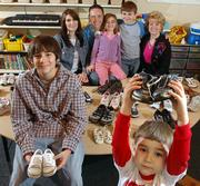 Sgt. Joey Kean, Lawrence, who is in the Kansas National Guard and has been serving in Iraq, and his mother, Susan Mozykowski, are working to collect shoes to distribute to Iraqi children. Mozykowski, director at Sunshine Acres Montessori Preschool and Child Care Center, has posted a basket in the school where children have donated the shoes. Members of the family, from left, are Christian, 13, his mother, Danelle, Joey, Joplin, 5, London, 8, Joey's mother, Susan Mozykowski, and Jace Kean, 3. They're shown Friday at the school with some of the donated shoes.