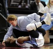 North Carolina's Ivory Latta writhes on the floor in pain as trainer Terri Jo Rucinski, top, comes to her aid. Carolina beat Purdue, 70-68, Sunday in Cleveland. Latta suffered a cramp in her left calf and wasn't expected to miss UNC's next game - Tuesday against Tennessee.