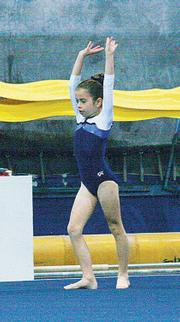 Natalie Rainbolt competes in the floor routine during the Winter Cup on Dec. 10 at Lawrence Gymnastics Academy.