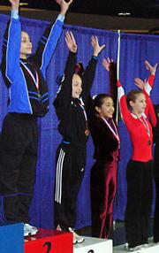 Abbey Bays raises her arms after receiving her medal for her third place vault finish at the state tournament.
