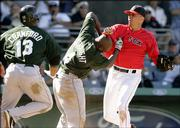 Boston Red Sox pitcher Julian Tavarez, right, lands a punch during a fight with Tampa Bay Devil Rays base runner Joey Gathright after he slid into Tavarez while trying to score on a hit by Julio Lugo in the eighth inning of their spring training baseball game in Fort Myers, Fla., Monday March 27, 2006.  Both benches cleared after the incident.  At left running to Gathright's aid is teammate Carl Crawford.