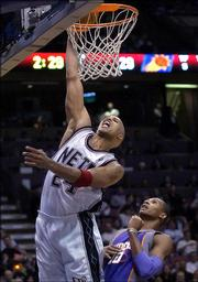 New Jersey Nets' Richard Jefferson, left, dunks the ball as Phoenix Suns' Leandro Barbosa, of Brazil, looks on during second quarter NBA basketball Monday night, March 27, 2006 in East Rutherford, N.J. Jefferson scored 16 points as the Nets beat the Suns, 110-72.