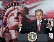 "President Bush speaks to newly naturalized citizens at a naturalization ceremony at the Daughters of the American Revolution administration building in Washington Monday, March 27, 2006. President Bush said Monday that overhauling the nation&squot;s immigration laws ""is not going to be easy"" and warned critics against stoking anti-immigrant feelings by calling them a threat to the nation&squot;s identity or a burden to the economy."