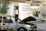 Iraqi men survey the site of a U.S. backed raid on a Shiite neighborhood in Baghdad Monday March 27, 2006 in Baghdad. At least 16 Iraqis were killed in a U.S. backed raid in a Shiite neighborhood of the capital on Sunday evening.