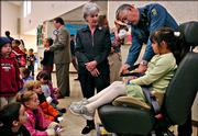 Adyson Crough, 5, a kindergartner from Indian Hills Elementary school and Kansas Highway Patrol Trooper Tim McCool demonstrate for Gov. Kathleen Sebelius how to use a booster seat Monday, March 27, 2006, at the Susanna Wesley Church in Topeka, Kan., after the governor signed the new booster seat law.