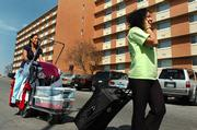 Kansas University freshman Kristina Kraft, Oklahoma City, right, and freshman Camille Cushinberry, Topeka, move a carload of clothes brought from home during spring break Wednesday into McCollum Hall.