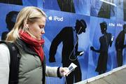 Hedwig Pagmar Hansson, a tourist from Stockholm, Sweden, listens to an Apple Video iPod as she walks next to an iPod advertisement Wednesday in downtown San Francisco. Owners of recent iPods will now be able to set how loud their digital music players can go. Apple Computer Inc. is making the setting available as part of a new software update. People concerned about hearing loss have welcomed the change.