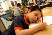 Sabian Bray, a kindergartner at New York Elementary rests his head as he finishes an assignment Thursday morning. The state Senate Thursday, took up the school finance measure, which could assure Lawrence school district's plan of moving forward with all-day kindergarten.