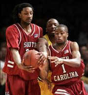 South Carolina's Renaldo Balkman, left, and Tre' Kelley, right, squeeze Michigan's Daniel Horton off from the ball in the second half during the championship game of the NIT Thursday, March 30, 2006 at Madison Square Garden in New York.  South Carolina won, 76-64.