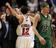 Chicago's Kirk Hinrich (12) gets a hug from coach Scott Skiles, left, as Boston's Delonte West (walks off the floor. Hinrich scored 23 of his 25 points in the second half and took a key charge late to help the Bulls win, 100-94, Saturday in Chicago.