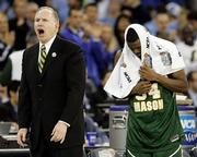 George Mason coach Jim Larranaga, left, yells at his players as Will Thomas covers his head with a towel. Florida beat the upstart Patriots, 73-58, Saturday in Indianapolis.