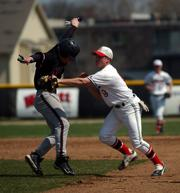Lawrence High's Marc Albers, right, tags out Lee's Summit North's Matt Cole. The Lions split a doubleheader in their home-opening series Saturday at Ice Field.