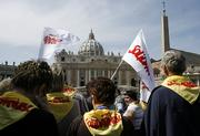 Polish pilgrims, wearing scarves and holding flags of the Solidarity pro-democracy movement, arrive in St. Peter's Square at the Vatican on Saturday, a day before the one-year anniversary of the death of Polish-born Pope John Paul II. Pilgrims have begun arriving in Rome to mark the first anniversary of John Paul II's death, praying by his tomb and preparing for an evening vigil in St. Peter's Square today to commemorate the exact time of his passing. In the background is St. Peter's Basilica.