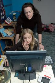 Dominie Haas watches as her daughter, Gabriel Ann, uses the Internet at home. Haas has had a problem with a person harassing her daughter online. The family now takes precautions that include never giving out any personal information online.