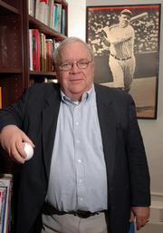 Jim Carothers, a Kansas University English professor, surrounds himself with baseball literature and memorabilia in his campus office, including a baseball from Fenway Park and a photo of New York Yankees legend Babe Ruth.