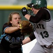 Free State High freshman Lexi Smith (13) narrowly dodges a tag from Shawnee Mission East second baseman Kim Chase. The Firebirds swept the Lancers on Tuesday at Free State.