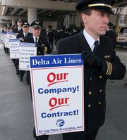 Delta Airlines pilots walk during an informational picket in March outside the Greater Cincinnati/Northern Kentucky Airport in a Hebron, Ky. Delta Air Lines Inc. pilots voted Tuesday to authorize a strike.