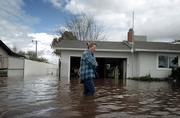 Brenda Frank stands outside her family's home in Merced, Calif., after a levee break caused many neighborhoods in the area to flood. Two levees broke Tuesday in California's chief agricultural region, flooding a trailer park, threatening other homes in Merced and inundating farmland near Sacramento.