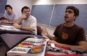From left, University of California, Irvine, student Greg Baker and Professor Michael Dennin listen to Samir Qurashi give a report during Dennin's class discussing the science behind superheroes. Dennin says he wants students to be able to apply the techniques they used to analyze comic book powers to evaluate the credibility of real-life scientific claims.