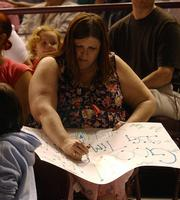 Kansas City, Kan. resident Teresa Sullivan puts together a sign in support of her brother, Tim Sullivan, Pomona, prior to the start of a deployment ceremony Thursday afernoon at the Kansas Expocentre in Topeka.