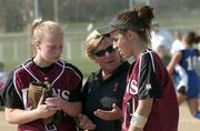 Lions softball coach Reenie Stogsdill, center, talks between innings with players Erin Miller, left, Drew Huff. The Lions defeated Olathe Northwest 3-2 in the first game of a double- header Thursday at Holcom Park.