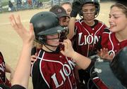 Erin Miller, foreground left, gets surrounded by her teamates after hitting a single to drive in the winning run in the last inning of the Lawrence Lions 3-2 win over Olathe Northwest Thursday at Holcom Park.