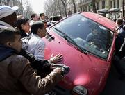 Protesters turn over a car after the motorist drove through a crowd of protesting students on Paris' Left Bank on Friday, April 7, 2006, injuring seven people. Furious demonstrators overturned the car and tried to kick its windows out. France's students have been protesting for weeks over a new law that will make it easier for companies to hire and fire people under age 26.
