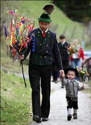 Dressed in traditional Bavarian highland attire, a German boy and his father carry their bouquets of decorated catkins in Ramsau, southern Germany. They were taking the bouquets to church for consecration, following an old tradition on Palm Sunday.