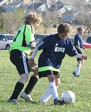 KVSA Club Select player Dante Tucker attempts to sneak the ball past a Green Dragon player. Club Select was unable to get the Saturday morning win at Youth Sports Inc.