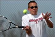 Lawrence High senior Ryan Robinson returns a serve during doubles play against Free State at Free State High School.