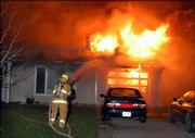 A fire at 2003 Emerald Drive near the Kansas University campus tore through the home's roof late Monday and may have spread to other parts of the house as well.