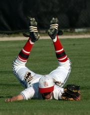 Lawrence High's Brian Heere flops after catching a pop-up in the second inning. Despite the defensive gem, the Lions fell to Free State, 12-1, Tuesday at Ice Field.