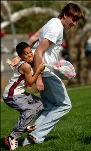 Nickolas Passmore, 8, clutching a bag of Easter eggs, tries to bring down Matt Owings, Overland Park, for a dollar bill. The Sigma Alpha Epsilon fraternity and the Chi Omega sorority put on an egg hunt for the Boys and Girls Club of Lawrence in one of many Easter-related events around the city. Saturday's events included the annual South Park egg hunt.