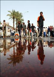 An Iraqi man looks at a bloodied puddle left after a car bomb explosion Saturday April 15, 2006 in Baghdad, Iraq.  A car bomb exploded near a restaurant frequented by police in eastern Baghdad at lunchtime, killing at least five civilians and wounding nearly 25 people, including four policemen, officials said.