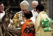 Pope Benedict XVI, center, baptizes a Japanese faithful during the Easter Vigil ceremony in Saint Peter's Basilica at the Vatican, Saturday, April 15, 2006.