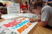 Kathanna Culp, center, and Alisha Ashley, both Kansas University seniors, work on signs for a planned march tonight by members of KU's ACLU chapter to city hall. The group has concerns about the city's noise ordinance.