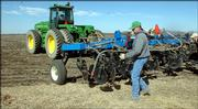 Todd Howard hooks up machinery with a fertilizer tank. Soaring fuel costs have made it more expensive for farmers to do business.